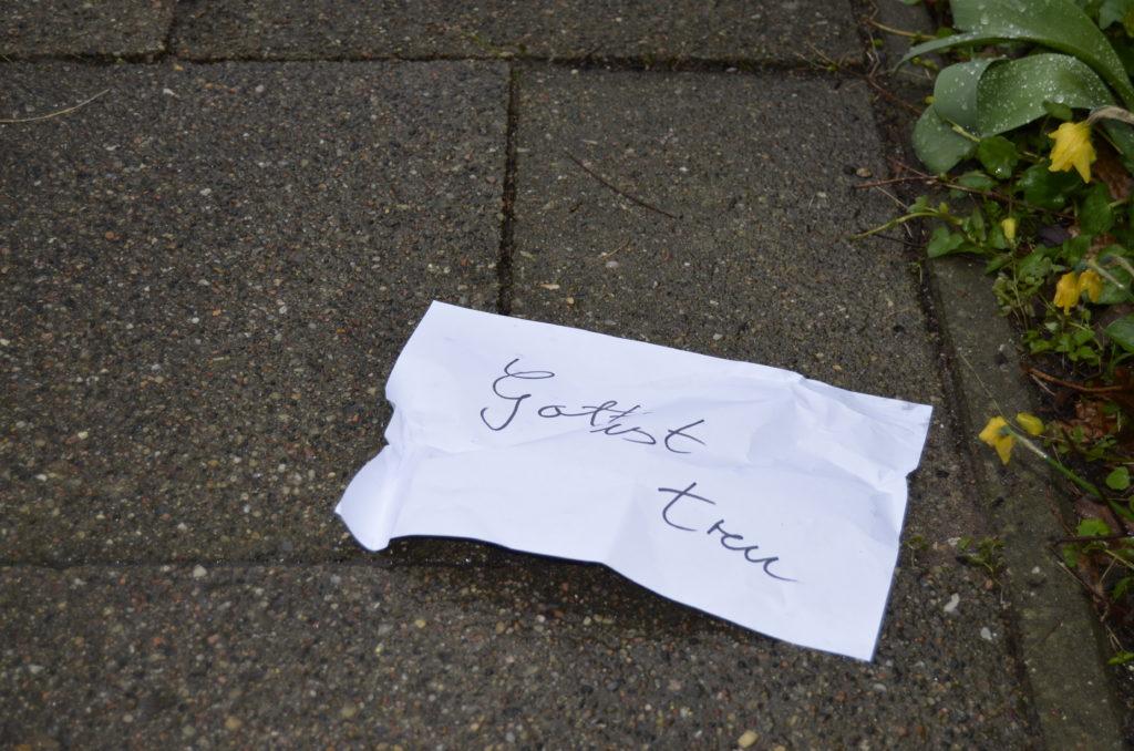 """Bild: Ein leicht zerknüllter Zettel auf dem nassen Boden, auf dem """"Gott ist treu"""" geschrieben steht."""